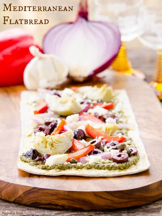 Mediterranean Flatbread is an easy to make meal or appetizer. It's loaded with pesto, artichokes, bell pepper, onion, olives and feta cheese.