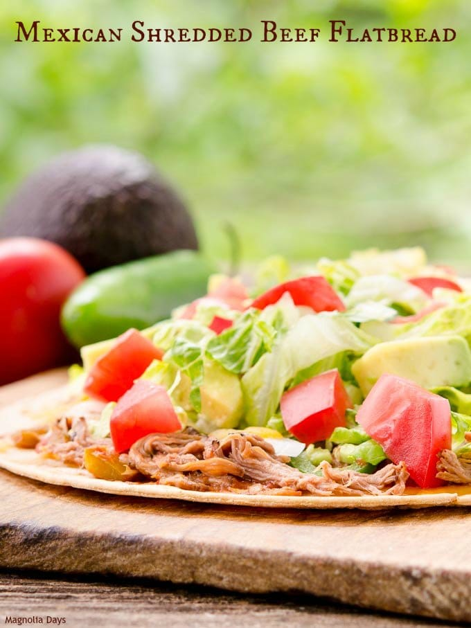 Mexican Shredded Beef Flatbread is piled high with onion, jalapeño, cheese, lettuce, avocado, and tomato. It's a tasty twist on a taco salad.