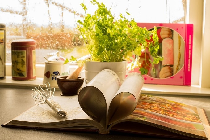 Cookbook, whisk, herbs in a sunny kitchen window