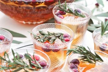 Clear punch glasses and bowl with green garnish and berries