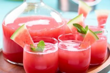 Watermelon mint agua fresca in a glass pitcher and cups