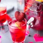 Clear glass of hibiscus punch with heart swizzle stick