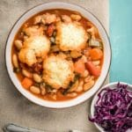 Bowl of pork belly casserole with dumplings and red cabbage with silverware