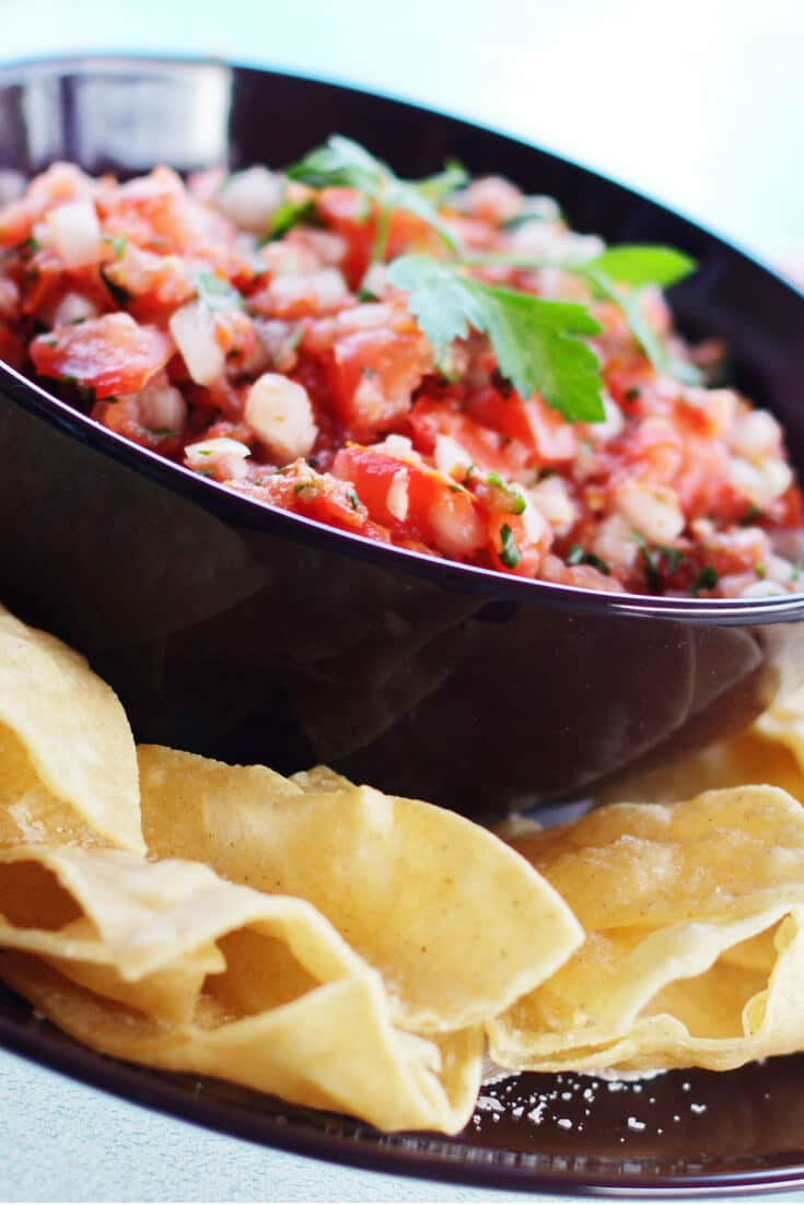 Pico de Gallo salsa in a brown bowl surrounded by tortilla chips