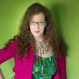 Photo of Katie Moseman in a green dress with pink sweater with jeweled necklace