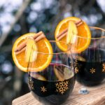 Two glasses of mulled wine with orange slices, ginger, and cinnamon