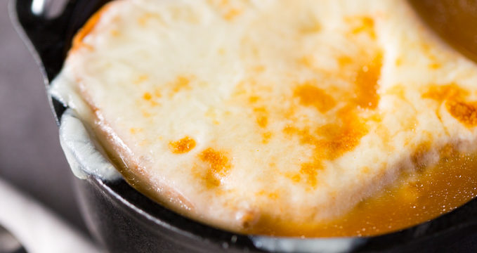 Closeup of melted cheese on a large soup crouton made from toast