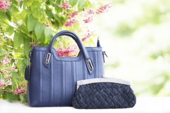 Two blue handbags outdoors to illustrate a Poshmark review