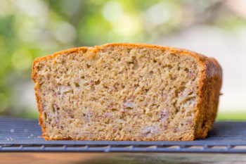 Interior of a loaf of sorghum flour banana bread resting on a rack with green background