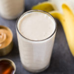Peanut butter banana smoothie in a glass next to ingredients