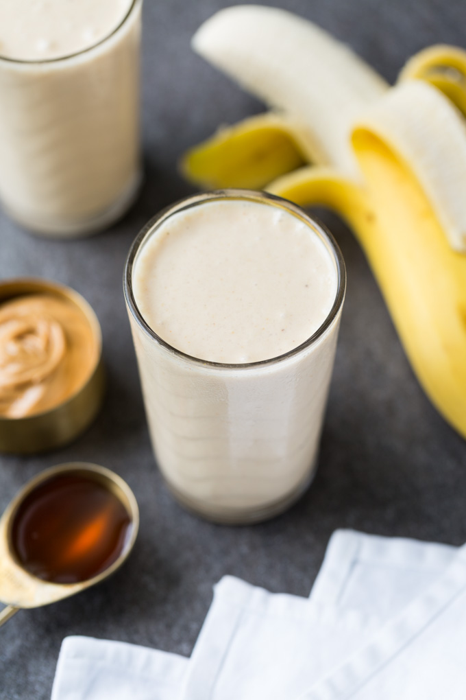 Peanut butter banana smoothie in a clear glass surrounded by peanut butter, honey, peeled banana