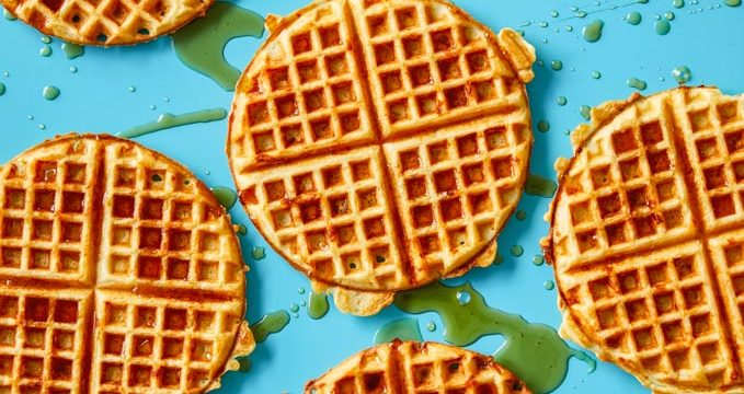 Cheddar waffles on a blue background with maple syrup dripped over them