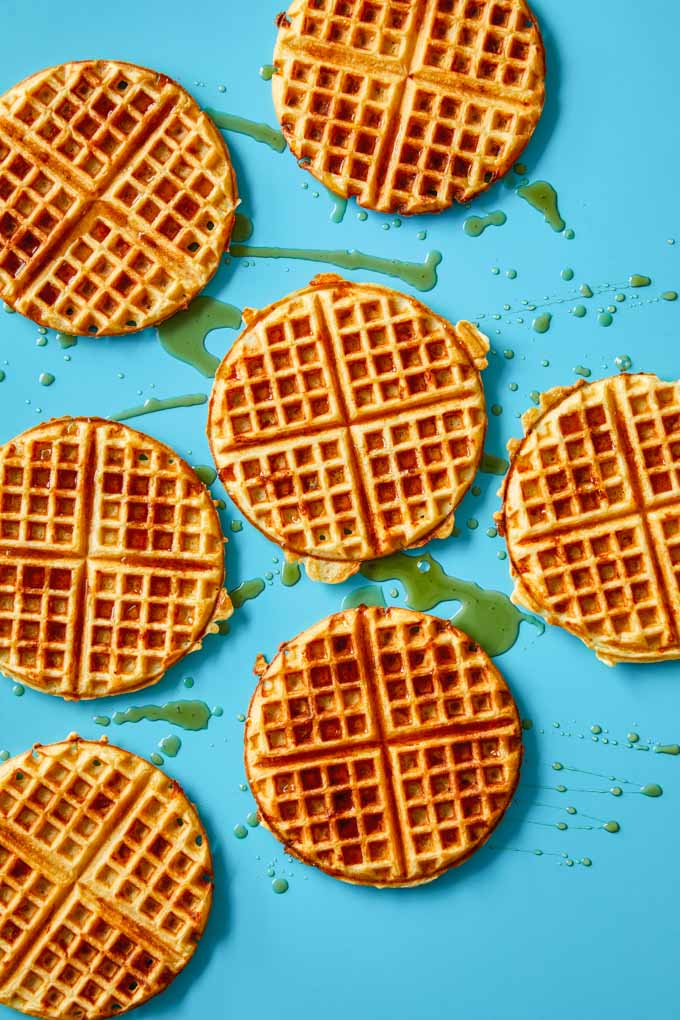 Cheddar waffles splashed with maple syrup on a blue background