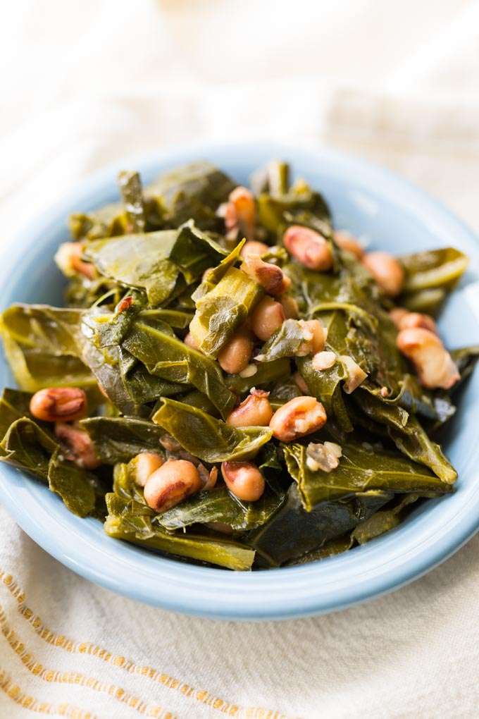 Hoppin john collard greens and black eyed peas in a blue dish on a cream colored cloth