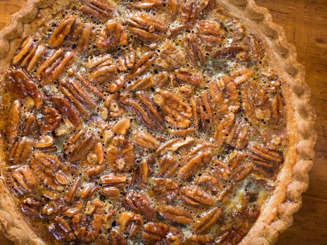 Whole Karo syrup pecan pie on a wood table