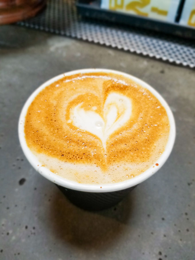 Heart in a to go cup of oat milk cappuccino