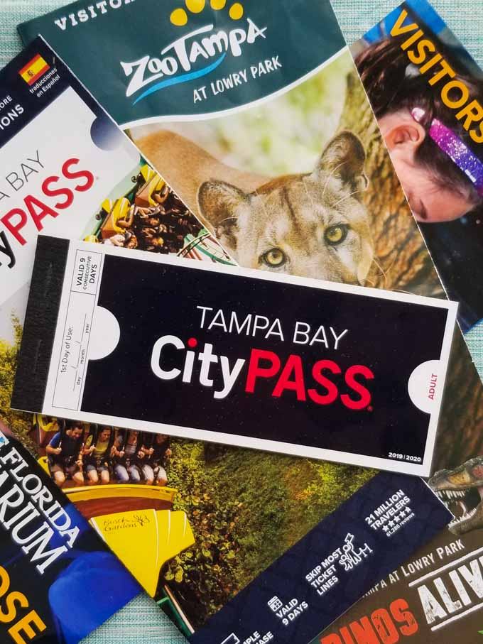 A Tampa Bay CityPASS voucher booklet on top of assorted attraction guidemaps