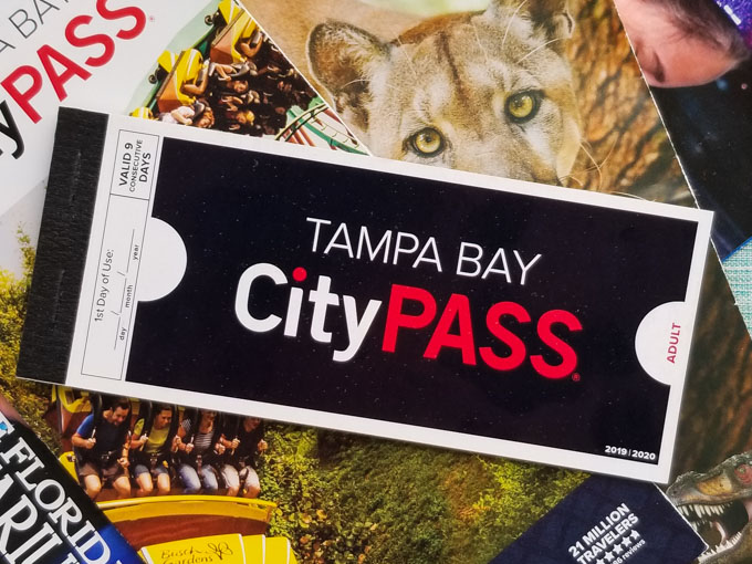 A Tampa Bay CityPASS paper voucher booklet on top of a ZooTampa guide and a Florida Aquarium guidemap