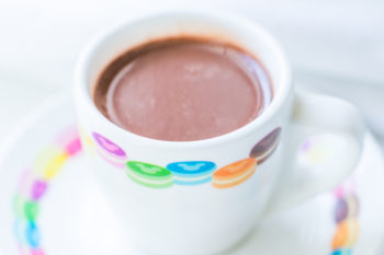 Closeup of hot chocolate in a white demitasse cup with rainbow macarons around the rim