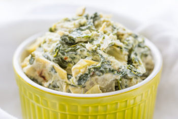 Closeup of easy spinach artichoke dip in a green ceramic ramekin on white cloth