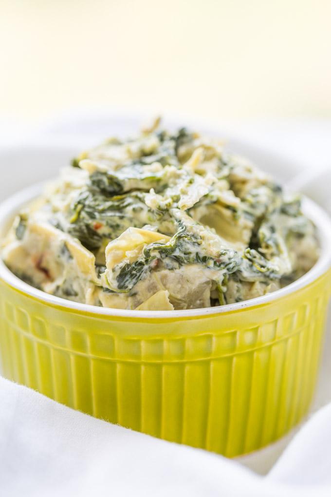 Easy spinach artichoke dip in a green ramekin on a white cloth