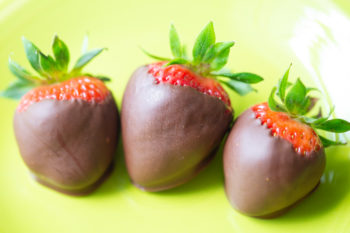 Three chocolate dipped strawberries on a green plate