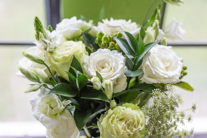 White and green UrbanStems bouquet in a yellow vase