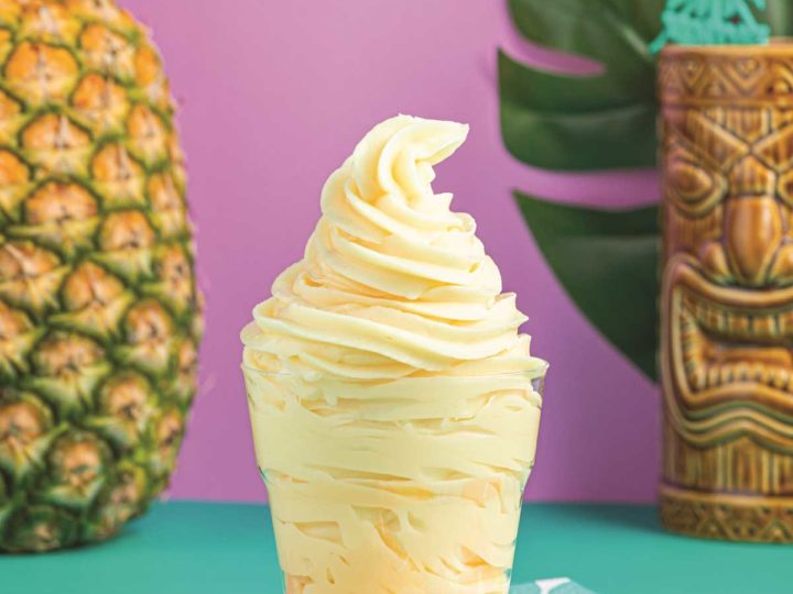 Clear cup of Dole Whip with a pineapple and a tiki glass in the background