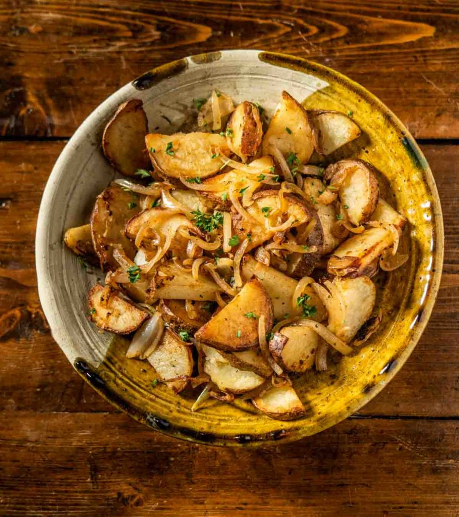 Lyonnaise potatoes in a rustic ceramic bowl on a wooden backdrop